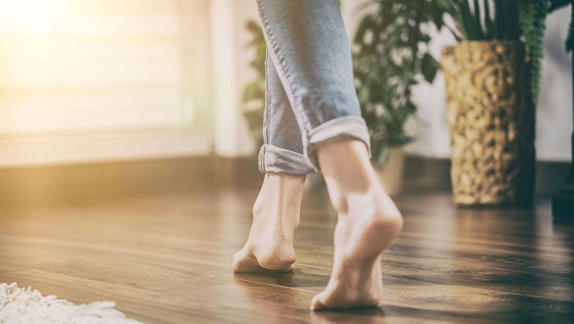 woman walking on wooden floor